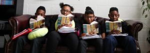 Aspire Memphis Students reading Bud Not Buddy on a couch